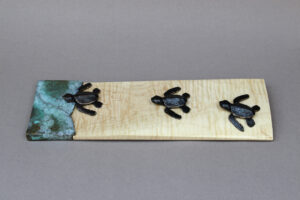 Three baby sea turtles heading out to sea. The turtles and the surf are bronze, and the sand is represented by a piece of curly maple.