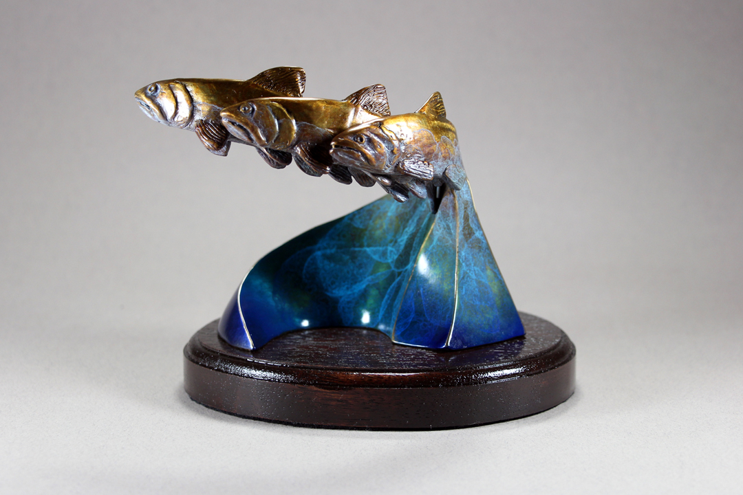 an abstracted sculpture of 3 Bronze Salmon migrating upstream