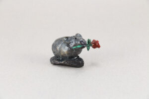 Small little bronze Pika with a flower in it's mouth.
