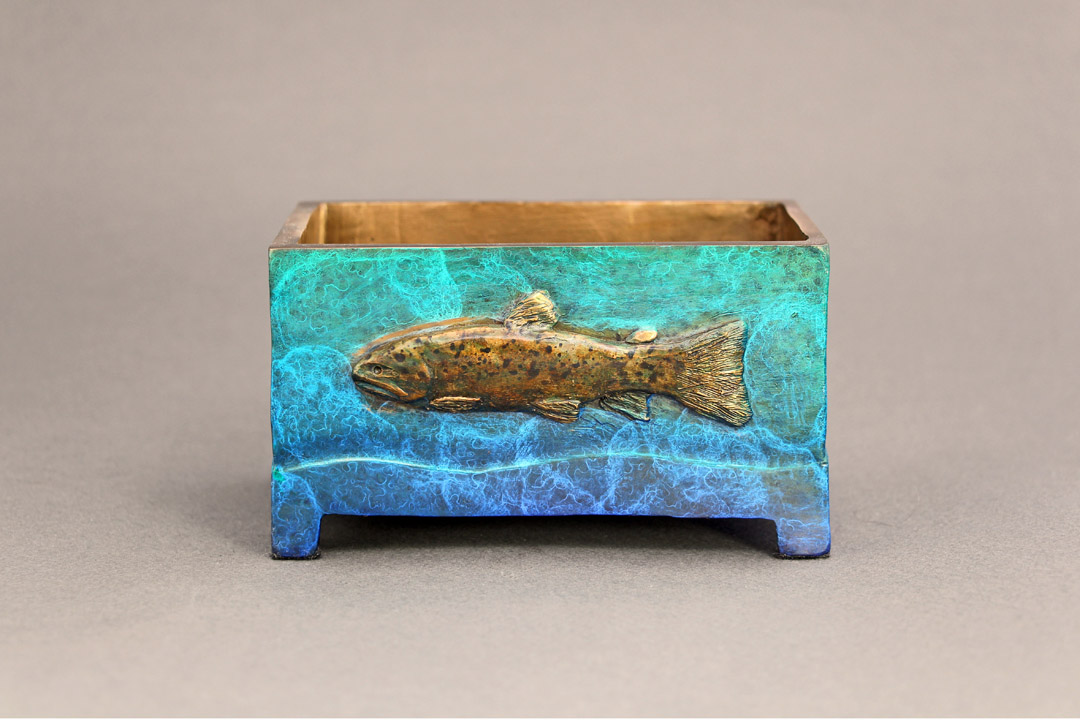 Small bronze box with a trout relief on either side.